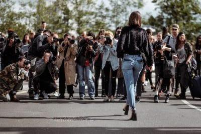 Kvinna framför en publik med kameror
