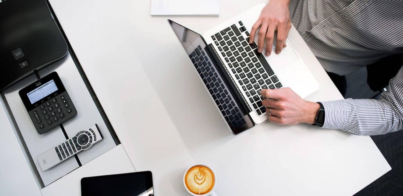 person med skjorta sitter vid ett vitt skrivbord med en macbook ur fågelperspektiv